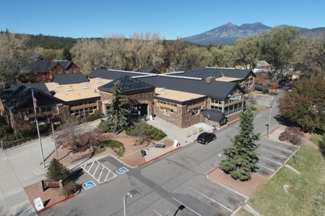 An image of the Flagstaff Library on Aspen Avenue from above showing the existing entry plaza and surrounding trees and the San Francisco Peaks in the background.