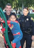 two police officers with child on playground